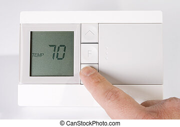 Thermostat - Stock image of hand adjusting thermostat
