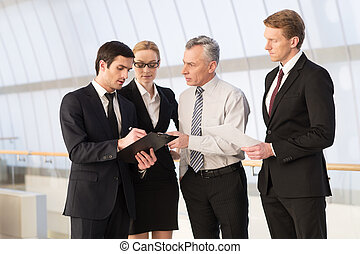 They all need an advice. Four business people discussing something while standing close to each other