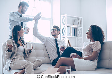 They deserve a little rest. Two handsome man giving high-five and holding coffee cups with smile while sitting on the couch at office with their beautiful coworkers