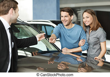 They have made a right vehical choise. Young car salesman giving a key from the new car to the beautiful young owners