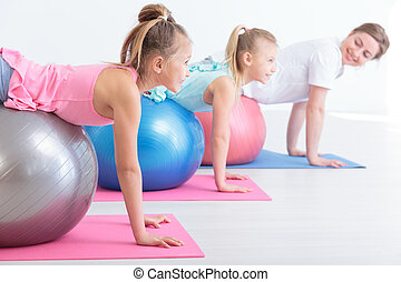 They like exercising with her - Cropped shot of two little...