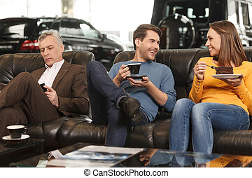 They need some break to make a right choise. Three car dealership customers having a break before making final decision about car they want