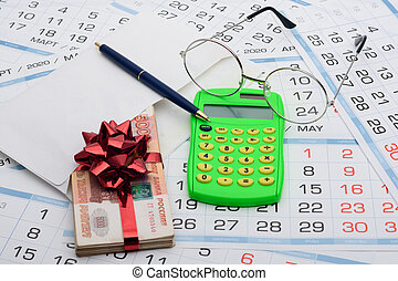 They put a wad of money in an envelope, rewound with a red ribbon and a bow, next to it lies a calculator, a pen, glasses and a background from calendars