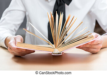 thick book in the hands of a woman on a close-up table