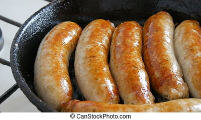Thick fatty delicious fresh sausages are fried in a pan in the home kitchen. Fried meat products making sausages for beer. White Munich or Bavarian sausages.