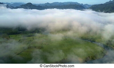 thick fog covers valley and bizarre mountains against sky -...