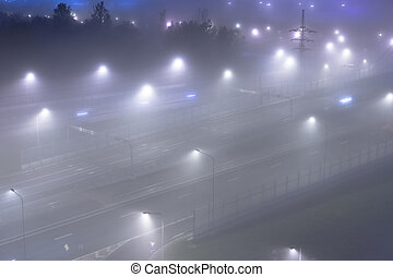 Thick fog over night highway in the city. View from above.