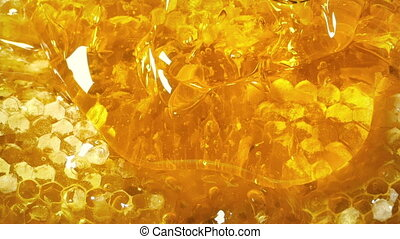 Closeup of thick golden honey dripping over honeycomb
