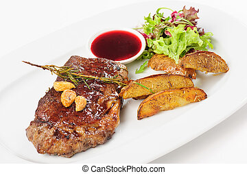 Thick juicy beef steak with potato and salad