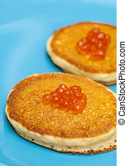 thick pancakes with salmon roe on blue plate