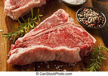 Thick Raw T-Bone Steak with Seasoning and Rosemary
