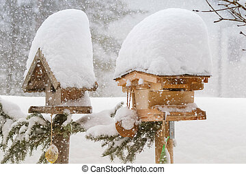 Thick snow falling on roof of wooden bird feeder during winter in Europe