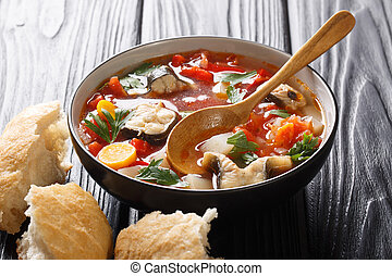 Thick tomato fish soup with eel and vegetables closeup in a bowl served with bread. horizontal
