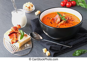 Thick tomato soup with basil and fried bacon in a black ceramic bowl on a grey abstract background. Healthy eating concept.