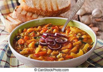 Thick Tuscan soup ribollita close up in a bowl. Horizontal -...