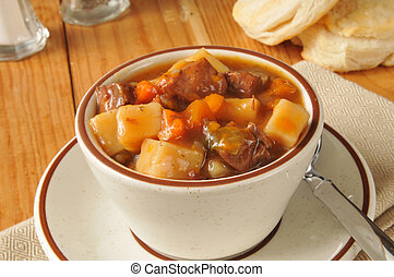 A cup of pot roast vegetable soup with fresh biscuits