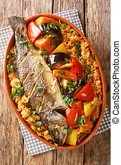 Thieboudienne Ceebu Jen Poisson au Riz a delicious one-pot meal with rice, fish stew and a variety of vegetables that is popular in Senegal closeup on the table. Vertical top view from above