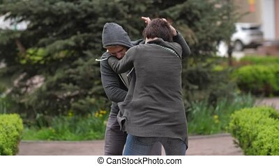 Thief attacking female intending to rob in park - Close-up...