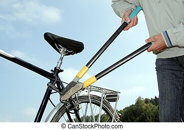 Thief braeking off a bicycle lock with a tool