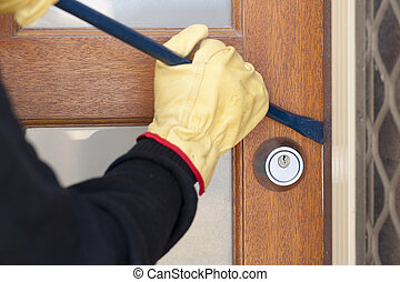 Thief breaking in house with crowbar - Burglar, thief with...