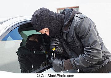 Thief breaking into a car
