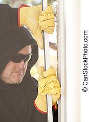 Thief breaking through window of house