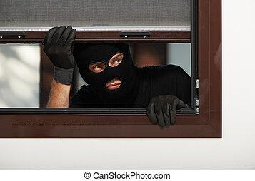 Thief Burglar opening window during house breaking