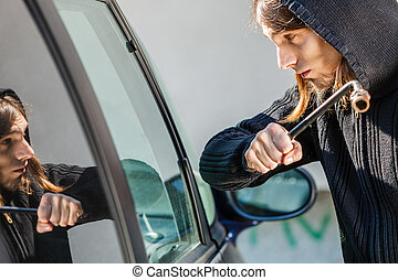 Thief burglar breaking smashing the car window