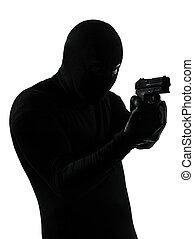 thief criminal terrorist holding gun portrait in silhouette...