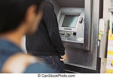 Thief folloing victim using a bank atm machine