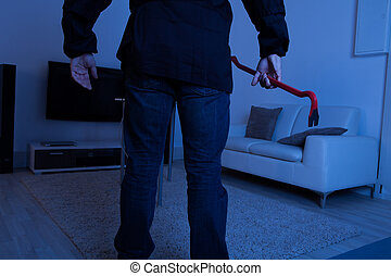Thief Holding Crowbar In Living Room - Midsection of thief...