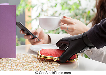 Thief stealing a wallet in coffee shop