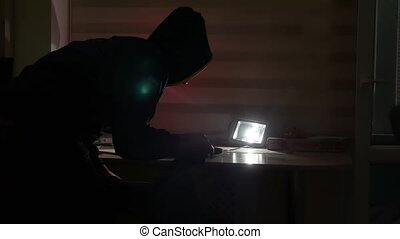 thief in a house silhouette at night indoor steals a laptop...
