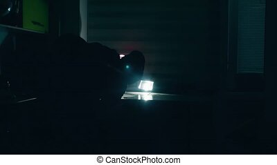 thief in a house silhouette at night steals indoor a laptop...