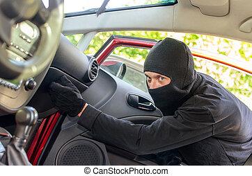 Thief in the mask breaks the door in the car