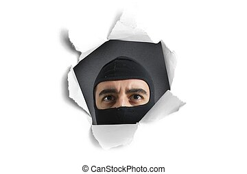 Thief looking through a paper hole