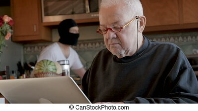 Thief lurking in a older man's home stealing his privacy data or online assets