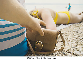 Thief stealing a bag from a woman on the beach.