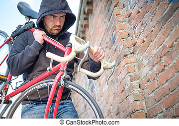 Thief stealing a bike in the city street