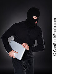 Thief stealing a laptop computer creeping furtively through ...