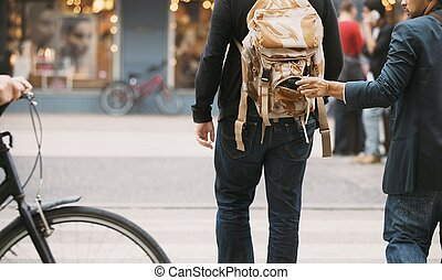 Thief stealing wallet from backpack of a man walking on ...