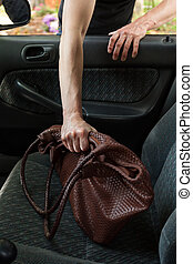 Thief stealing woman's bag from car, vertical