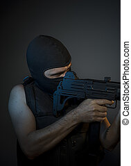 Thief Terrorist, a man dressed in a bulletproof vest and balaclava, is armed with pistols and machine guns