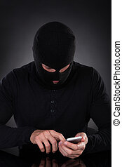 Thief trying to access a stolen mobile phone - Thief in a...