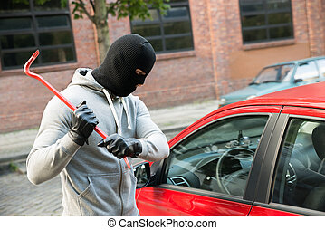 Thief Trying To Smash The Window Of The Car