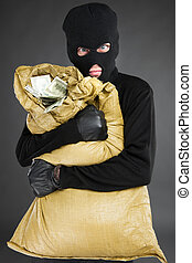 Thief with stolen goods. Front view of frustrated men in black balaclava holding a stolen money bag while standing isolated on grey