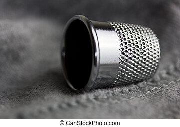 Thimble - A macro close up of a silver sewing thimble