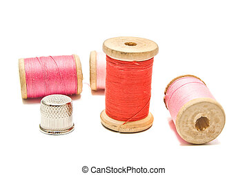thimble and spools of thread on white