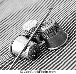 Thimbles and needle on a fabric .