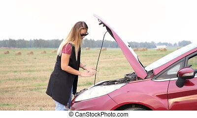 Thin blonde teenager pulls out the oil dipstick in her car engine to check the lubricant level.